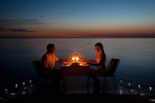 par, der spiser romantisk middag ved vandet