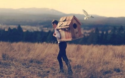 Man carrying a bird house on his back.