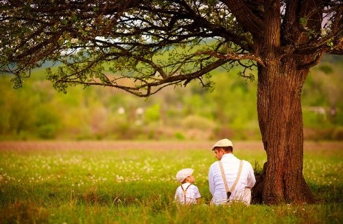 Father and son talking under a tree.