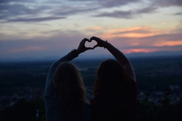 Two friends making a heart with their hands, showing Robert Cialdini's reciprocity principle.