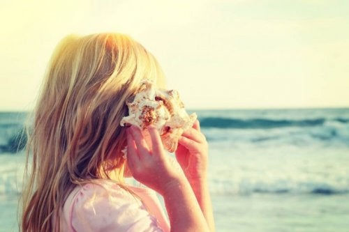 Selective attention shown through a girl listening to a shell at the beach.