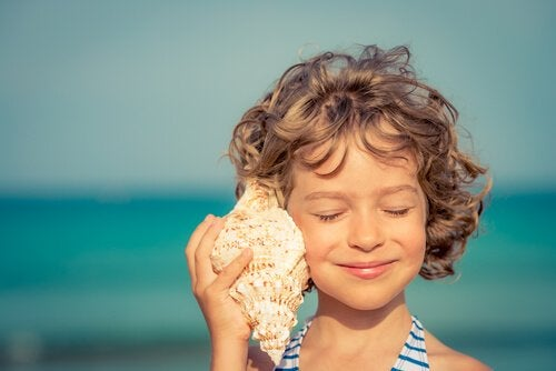 A girl listening to a sea shell.