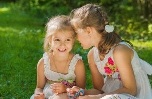 Two little girls smiling and talking.