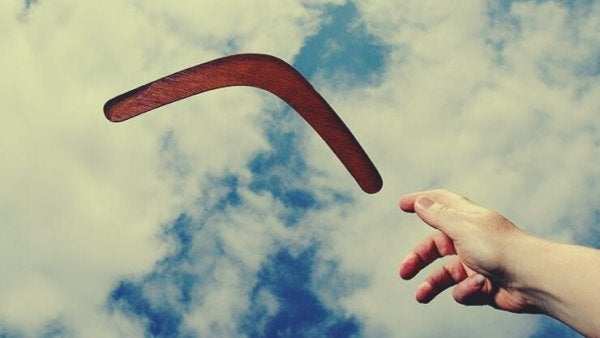 Hand throwing a boomerang, a metaphor for how you deserve the love you give to other people.
