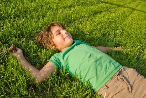 Little boy laying in the grass with a smile on his face.