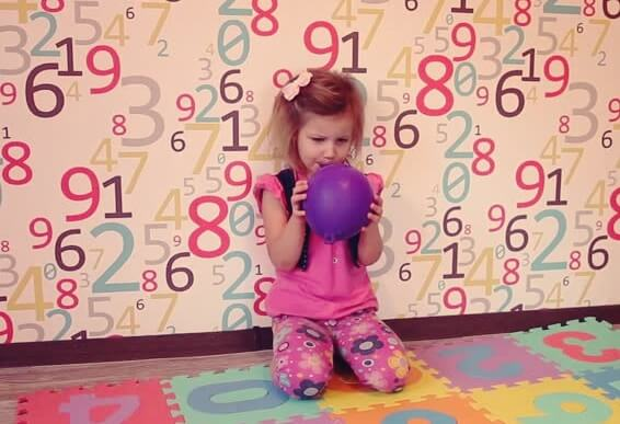 Little girl practicing balloon breathing.