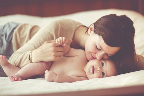 Mother kissing her baby in bed.