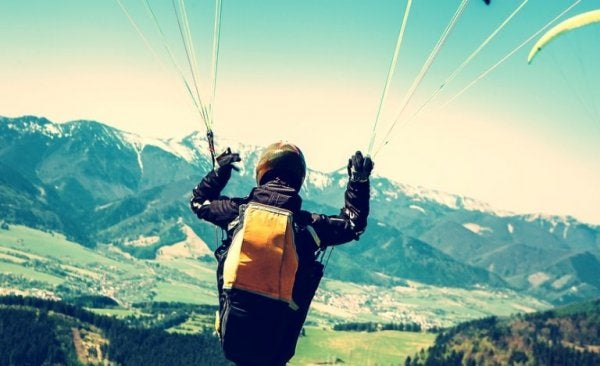 man flying through sky with parachute on