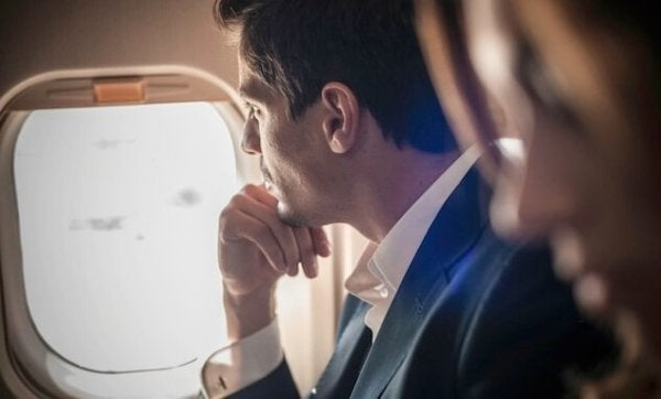 Man looking out airplane window.