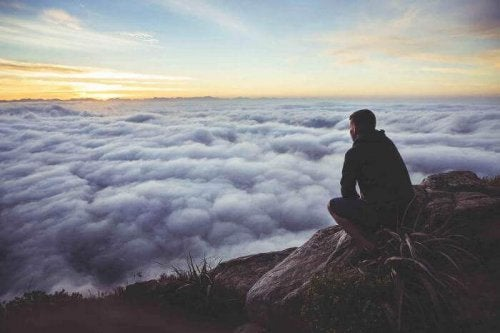 Man on a mountain looking down to a sea of clouds.