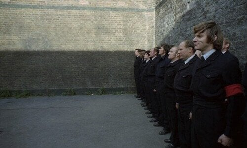 A Clockwork Orange still of men against a wall.