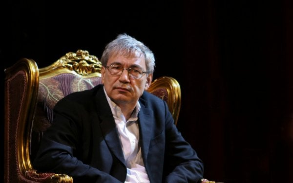 Orhan Pamuk sitting down reflecting on his works.
