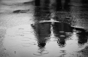 Puddle of water reflecting two elderly persons.