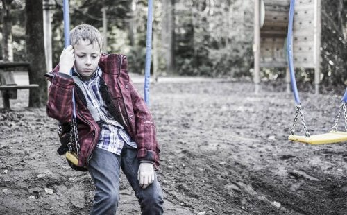 Sad boy sitting on a swing.