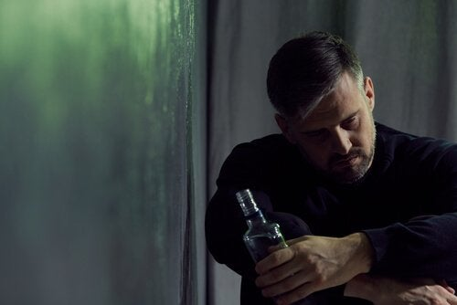 A sad man holding a bottle of alcohol.