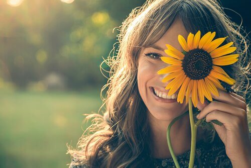 Smiling woman holding sunflower.