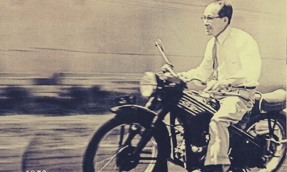 Soichiro Honda riding a motorcycle.