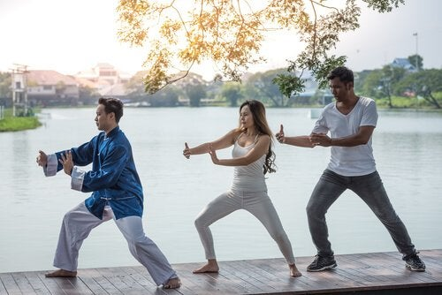 Three people doing qigong.