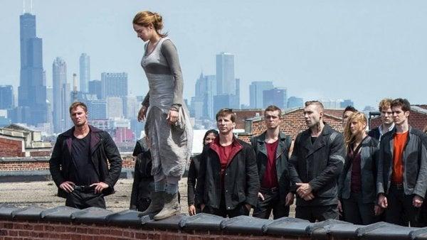 tilskuere der kigger på en kvinde der står på kanten af en mur