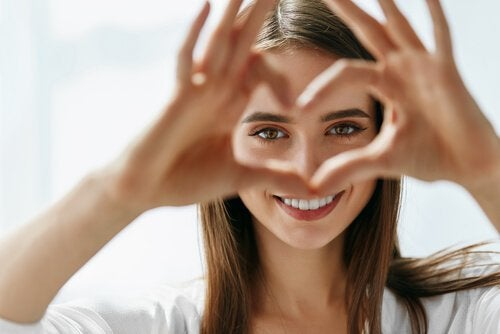 A woman making a heart with her fingers.