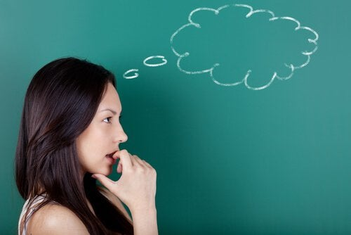 Woman thinking in front of a chalkboard.