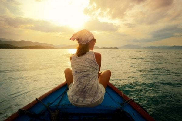 Woman who knows that traveling improves your brain health in a boat.