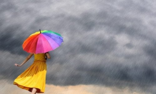 A woman with a colorful umbrella under a storm.