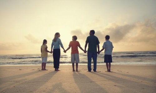 A family holding hands at the beach.