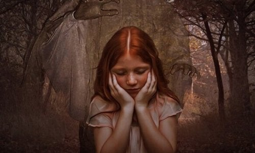 A redheaded girl in front of a forest.
