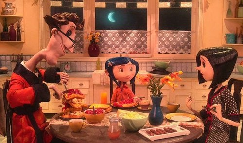 Coraline eating dinner with her parents.
