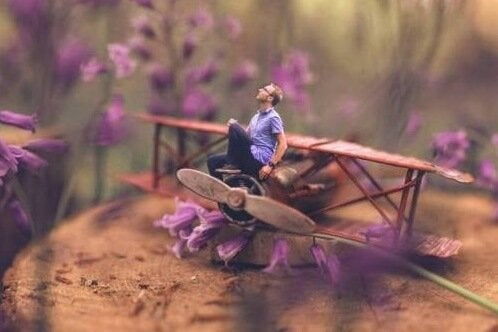 A guy sitting on a toy plane.