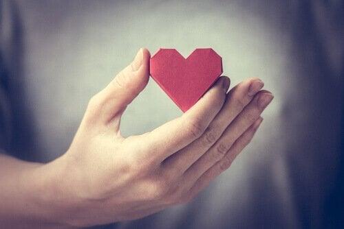 A hand holding a heart.