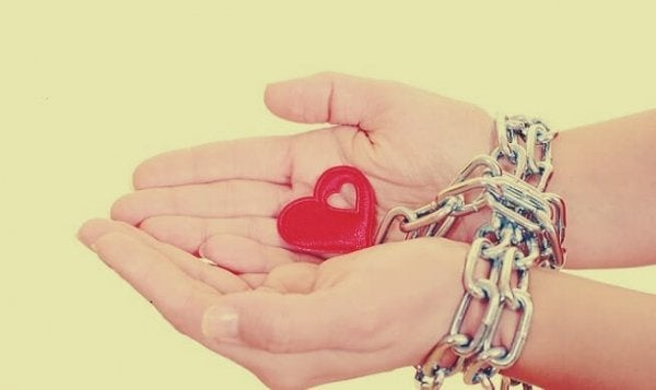 Hands chained to a heart.