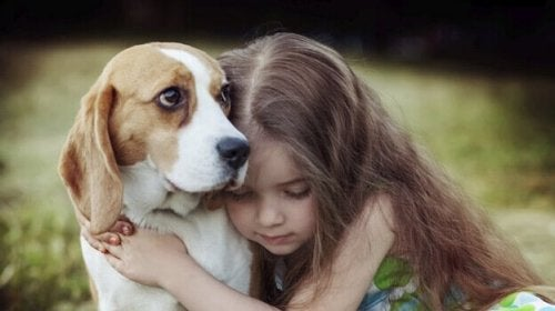 A girl hugging a dog.