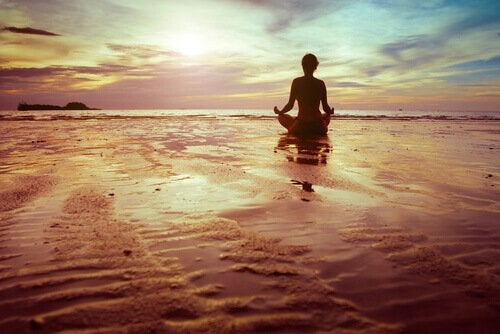 A person meditating on the beach.