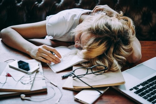 Tired woman with her head on the desk.