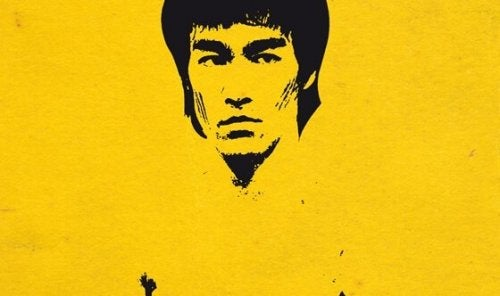 Painting of Bruce Lee on a yellow wall.