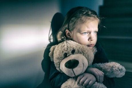 A girl holding a teddy bear.
