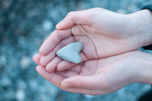 Person holding a heart-shaped stone.