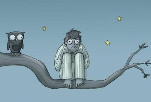 A boy, wide awake, next to an owl.