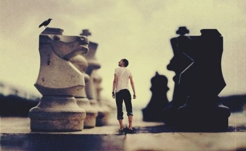 A man surrounded by giant chess pieces.