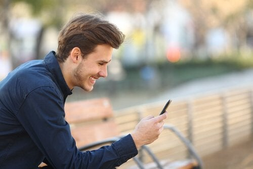 Man smiling and using phone.