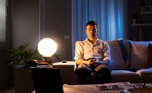Man with insomnia sitting on his couch.