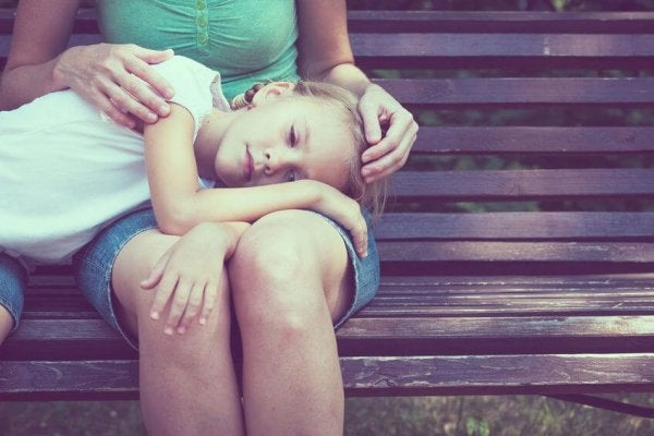 Sad girl with head on her mother's legs.