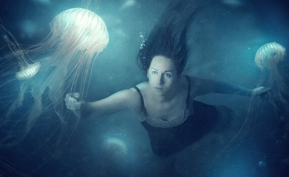 Woman swimming with jellyfish.