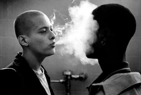 A white guy blowing smoke in a black guy's face.