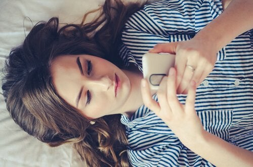 Girl lies in bed with phone.