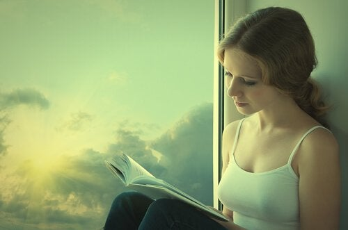 Girl reading book by the window.