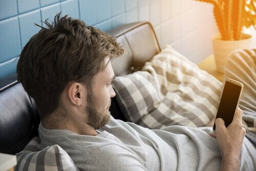 A guy looking at his phone, a habit that ruins sleep.