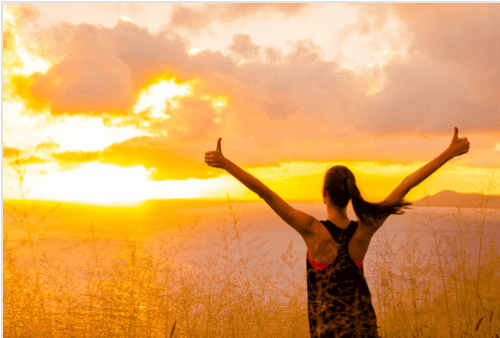 Motivated woman looking at the sunrise.
